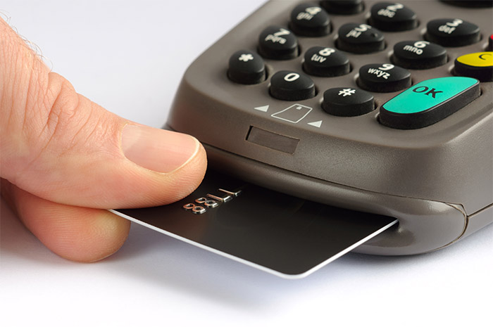 person taking their credit card out of a scanner